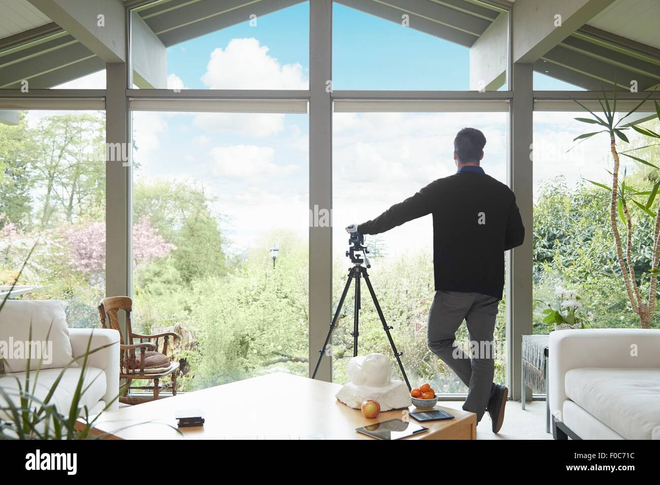 Rear view of man leaning on telescope looking out of window admiring garden scenic - Stock Image