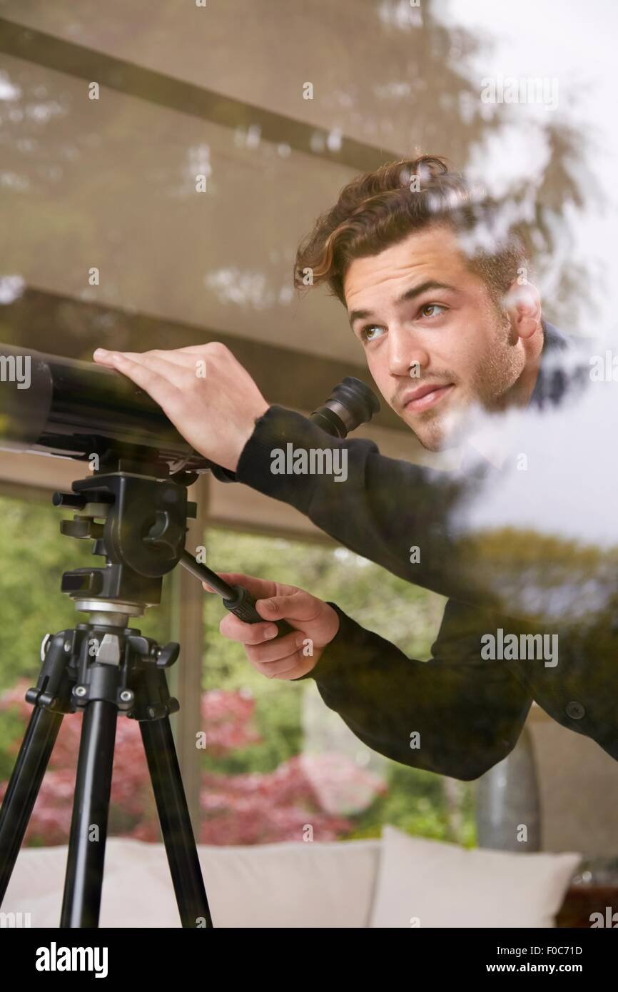 Portrait of man using telescope looking out of window - Stock Image