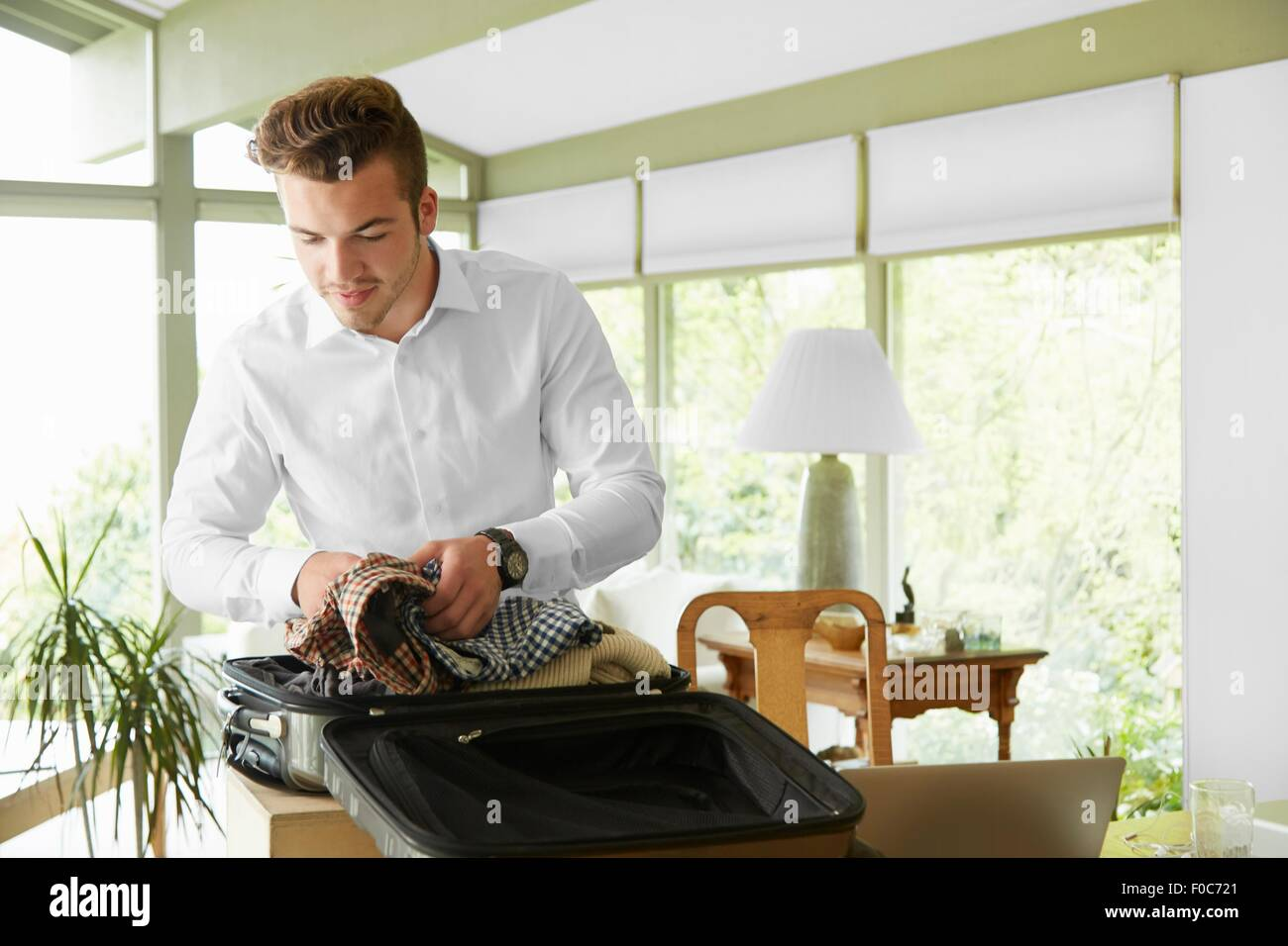 Businessman packing suitcase at home - Stock Image