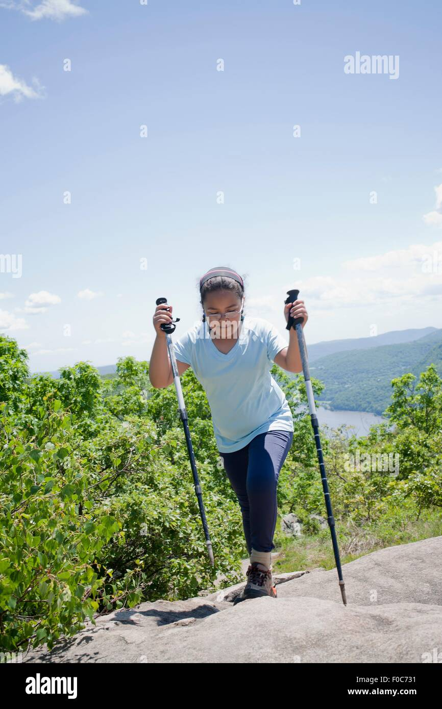 Young girl hiking up hilly landscape - Stock Image