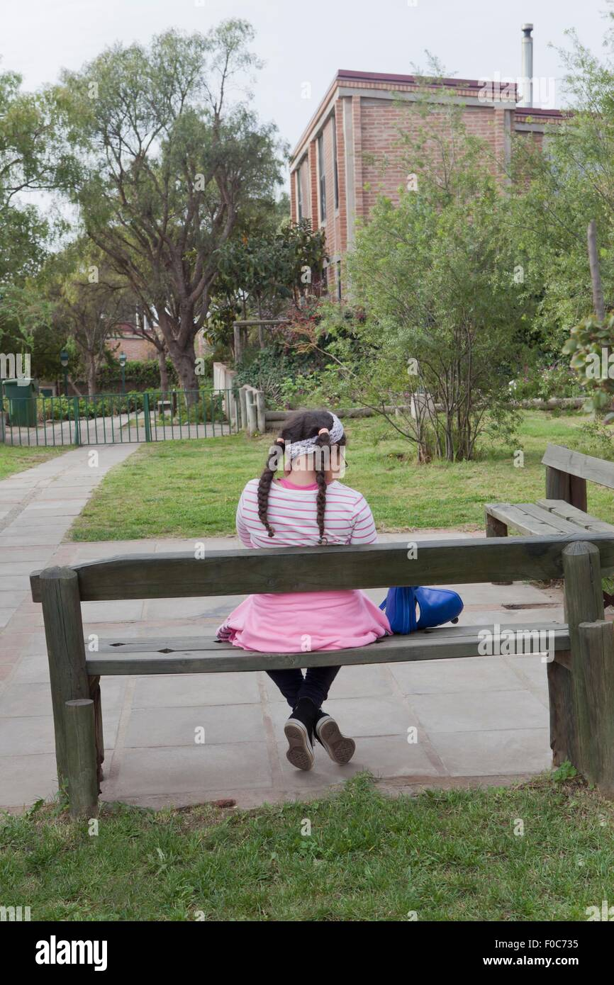Young girl sitting on bench, rear view - Stock Image
