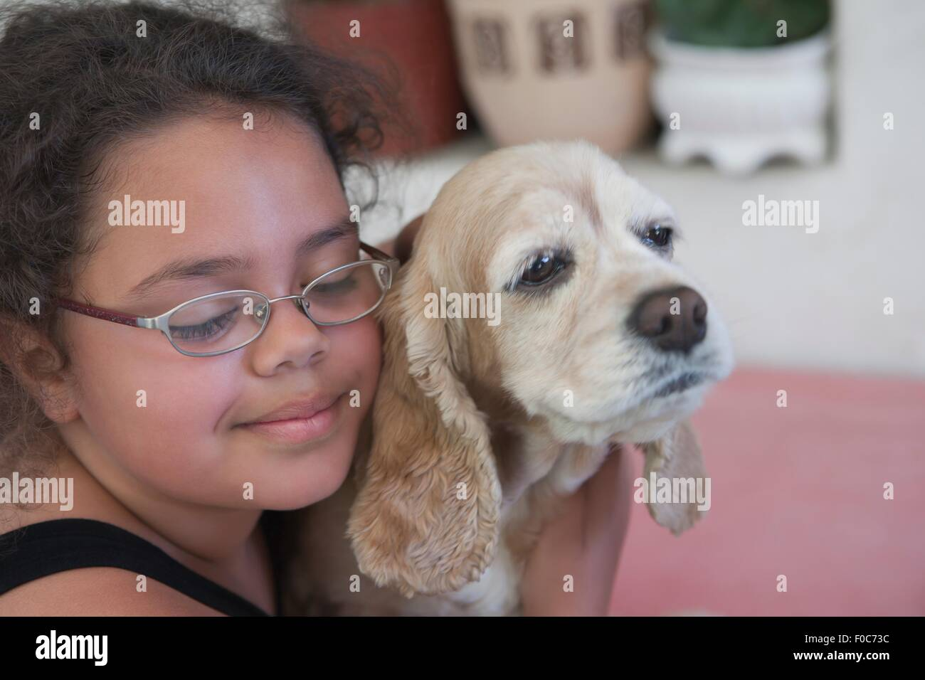 Young girl hugging dog, close-up - Stock Image