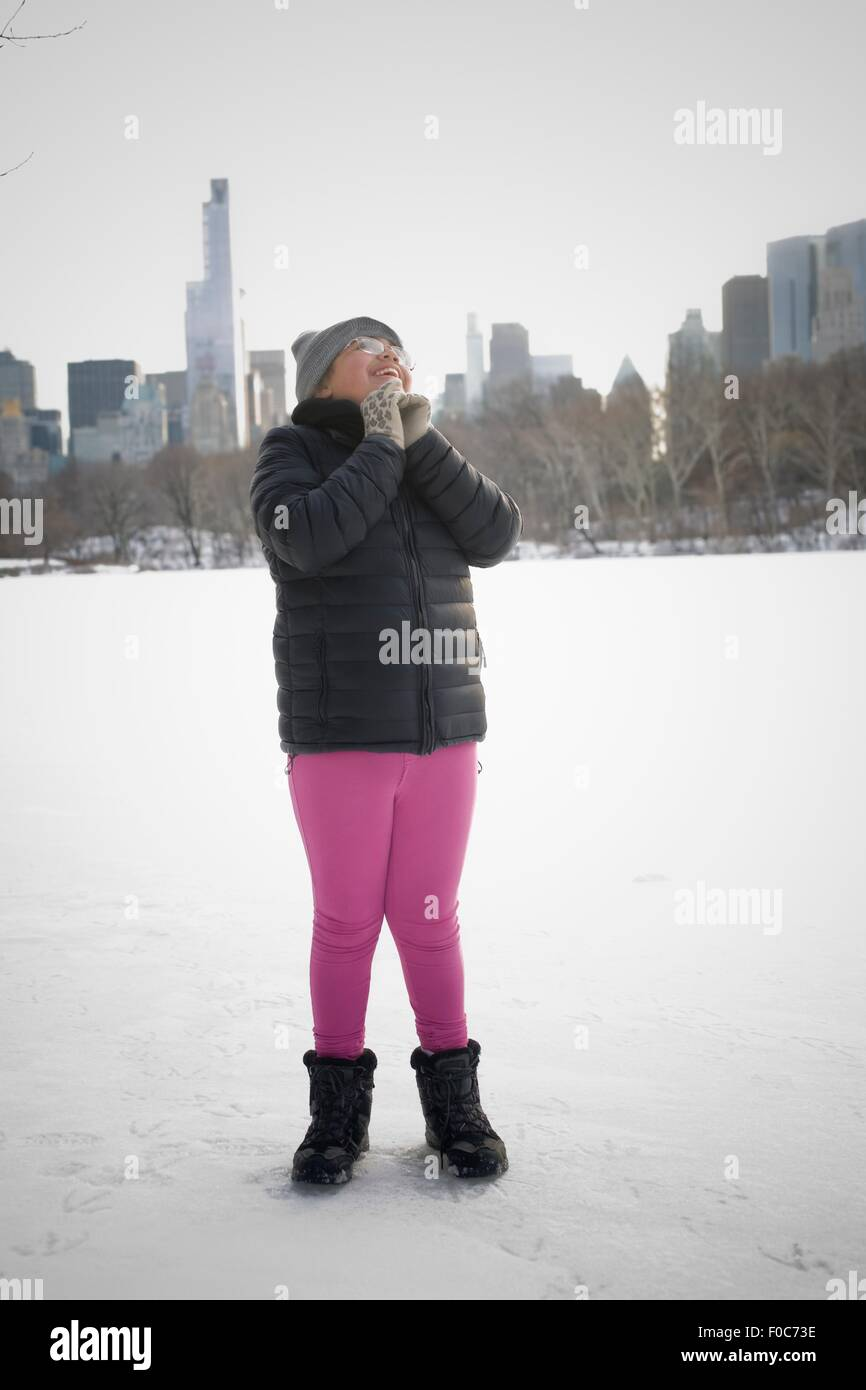 Young girl standing in snowy landscape, excited, New York, NY, USA - Stock Image