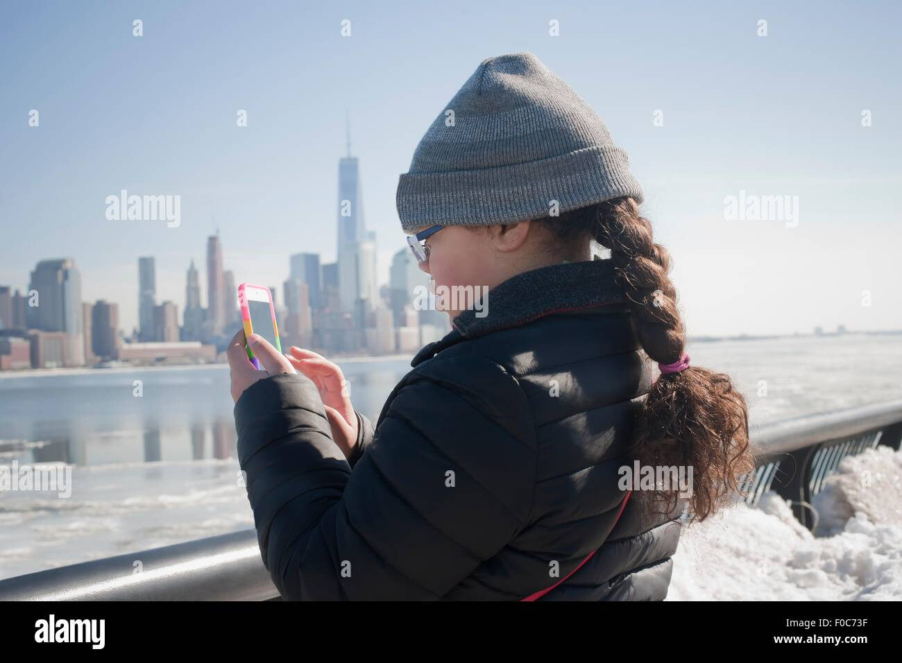 Young girl taking photograph of skyline using smartphone, New York, NY, USA - Stock Image
