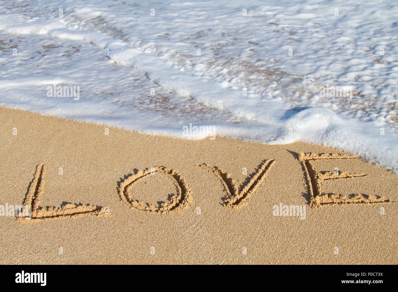 Love, written in sand, close-up - Stock Image