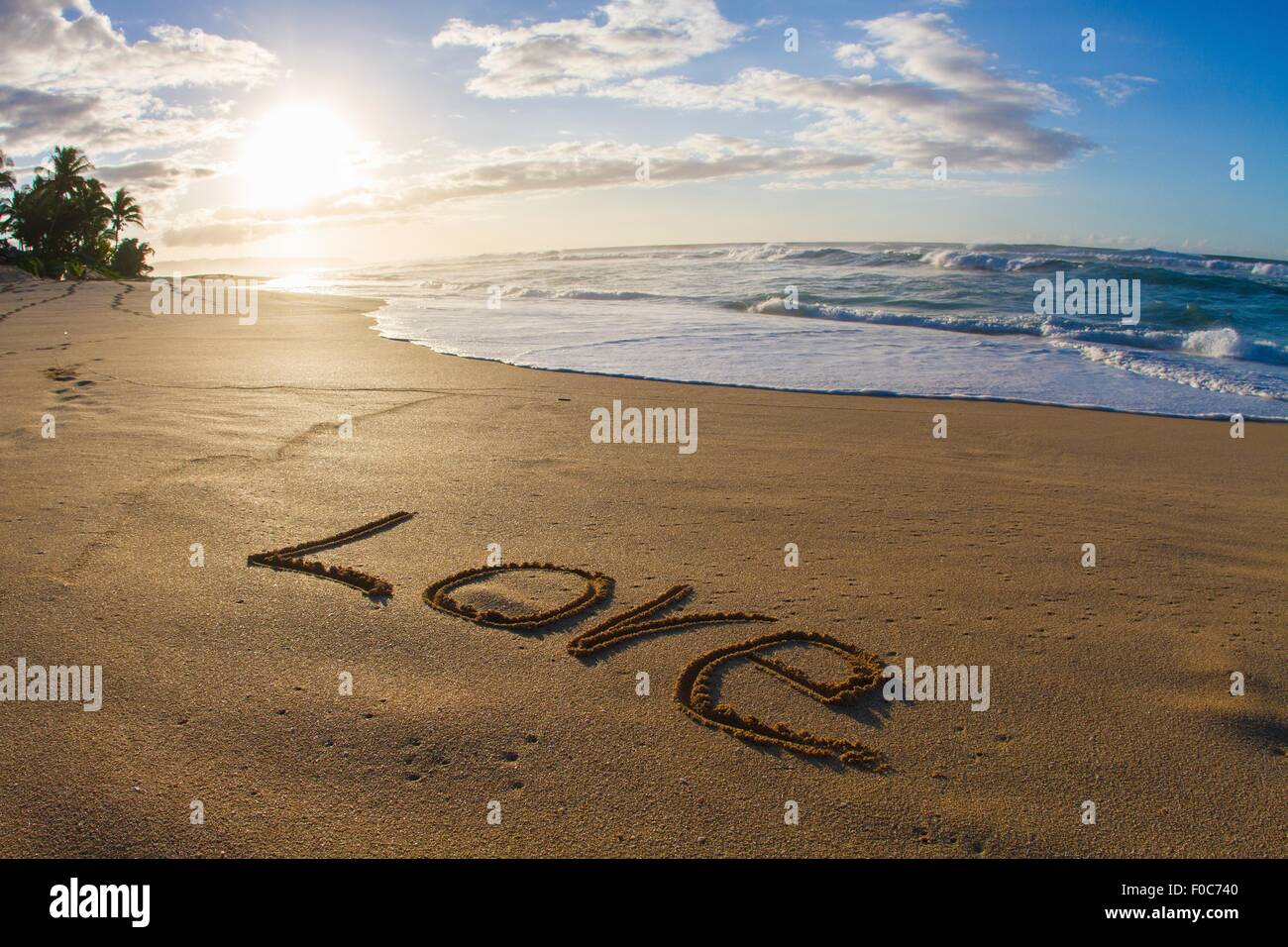 Love, written in sand, sunset - Stock Image