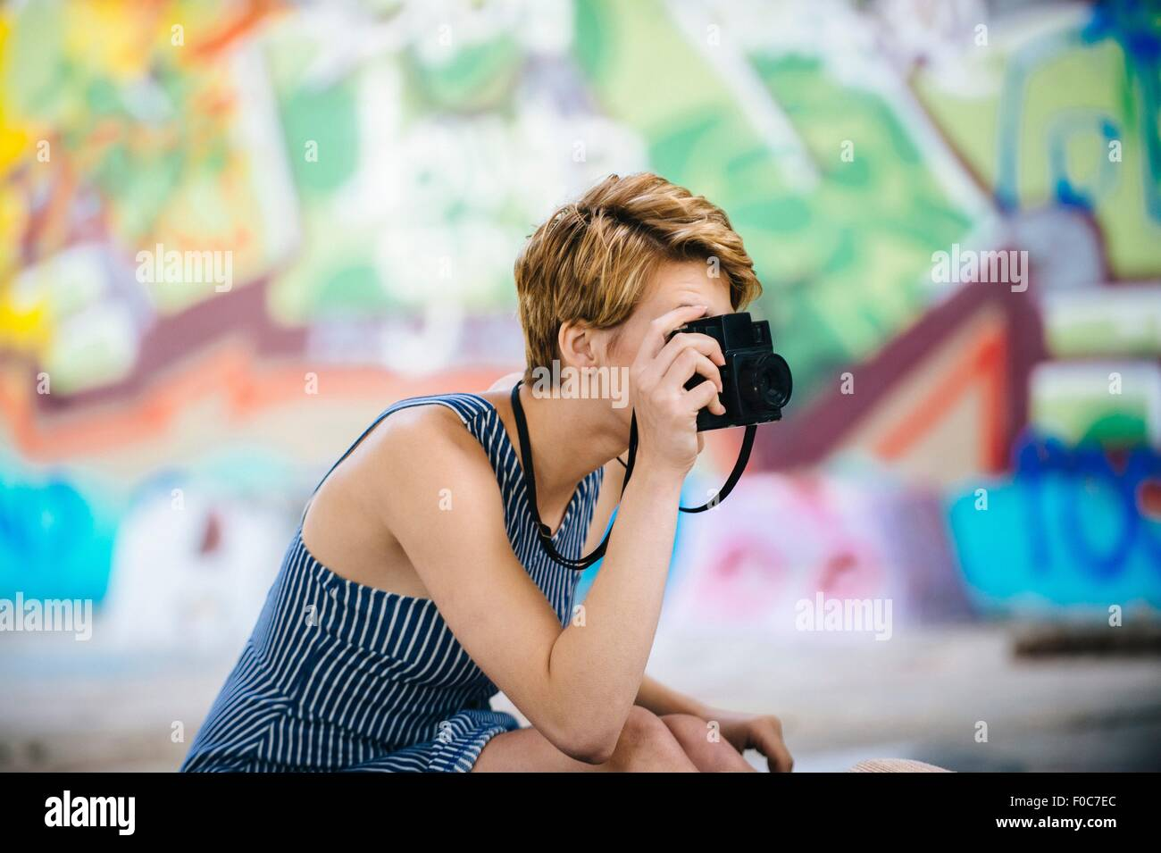 Stylish teenage girl photographing with camera in front of graffiti wall - Stock Image