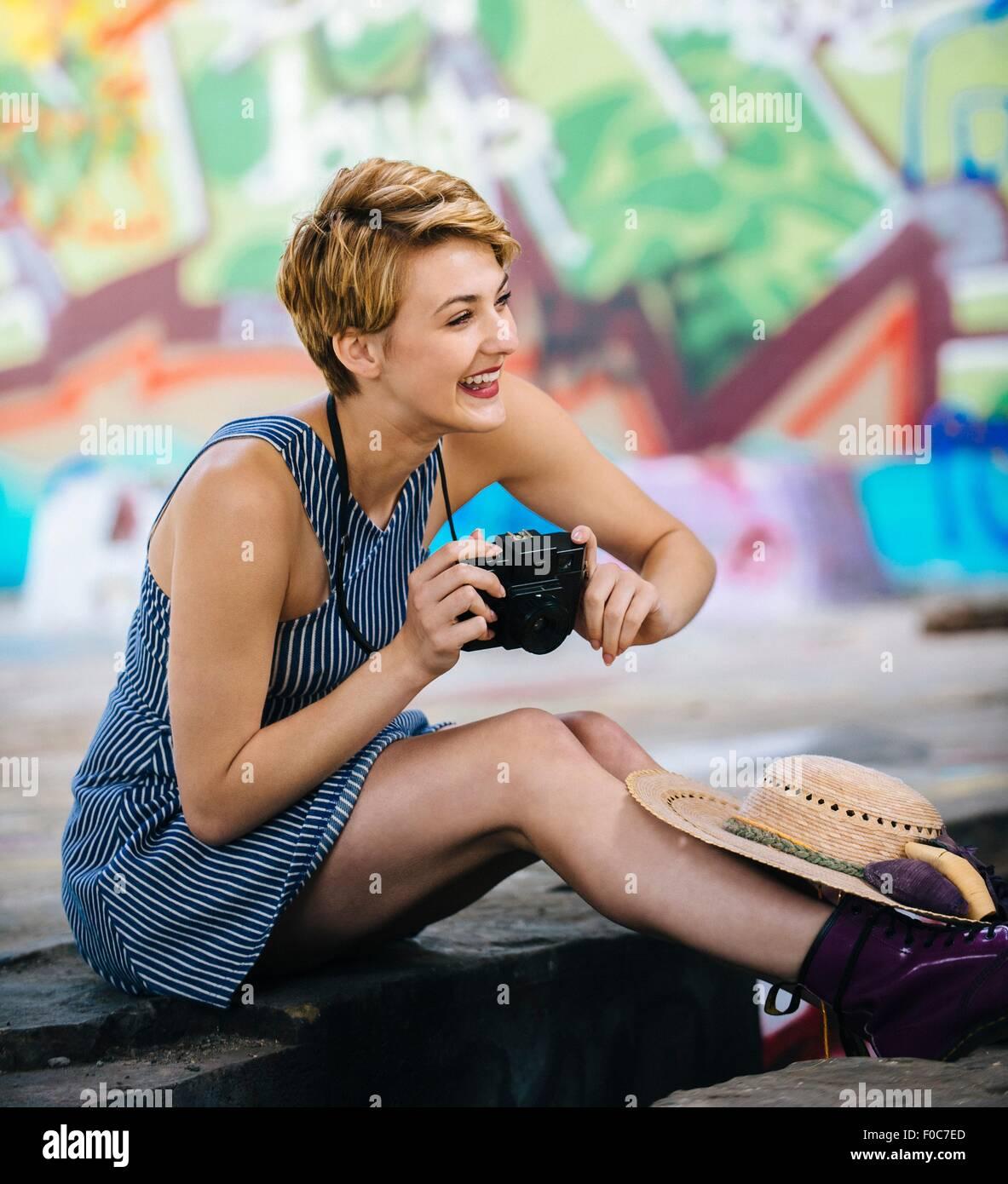 Stylish teenage girl sitting on sidewalk with camera in front of graffiti wall - Stock Image
