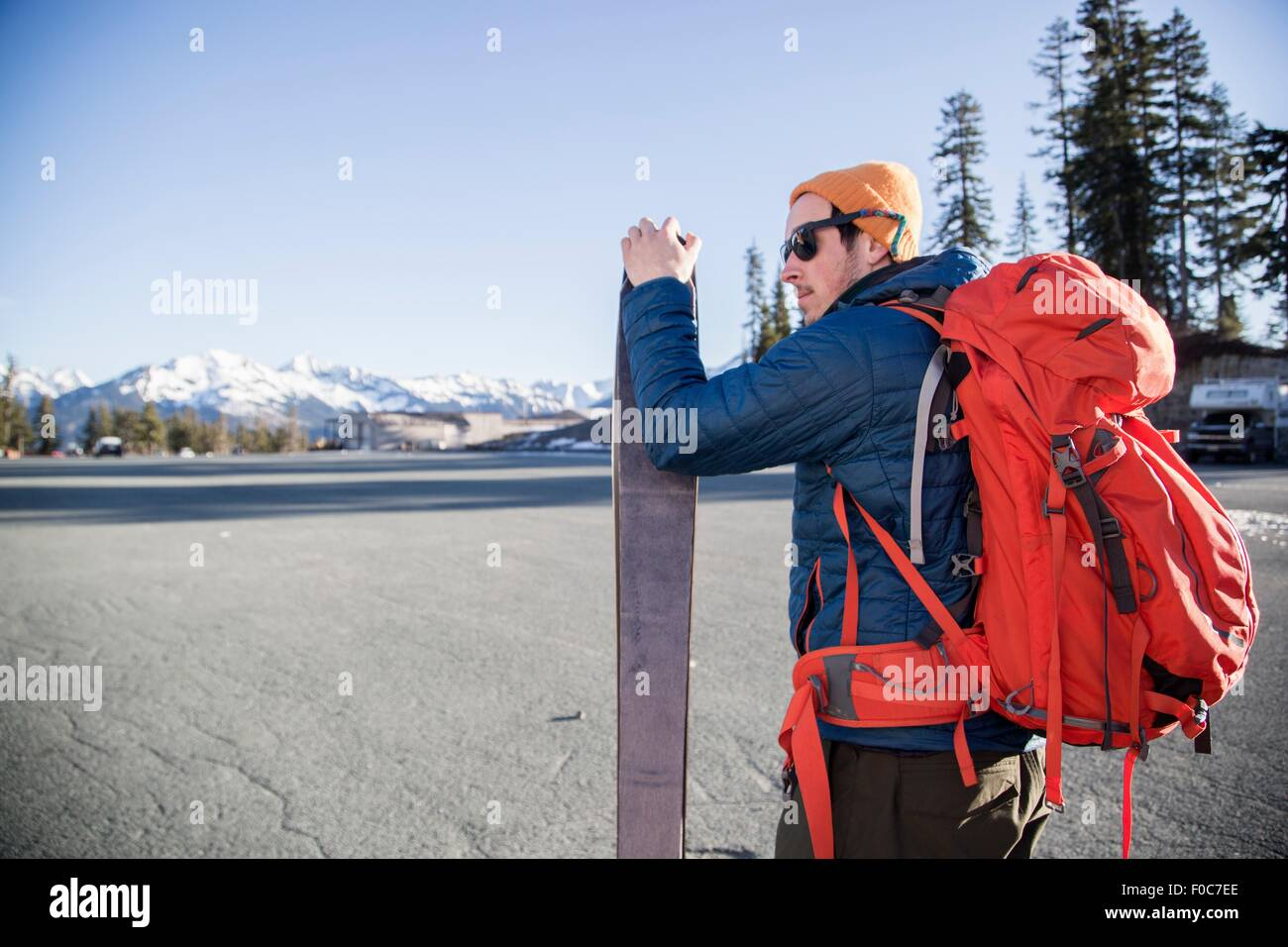 Young male skier in parking lot with distant snow capped Mount Baker, Washington, USA - Stock Image