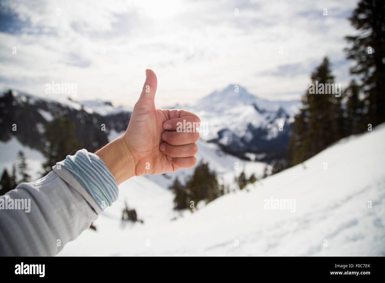 Female hand making thumbs up in front of snow covered view, Mount Baker, Washington, USA - Stock Image