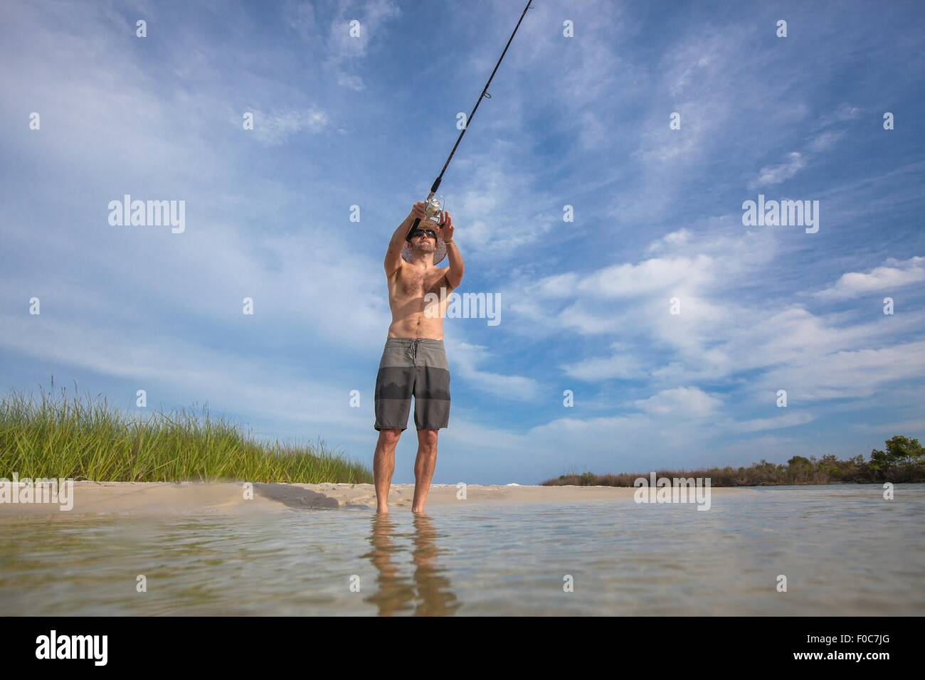 Low angle view of mature man fishing, Fort Walton, Florida, USA - Stock Image