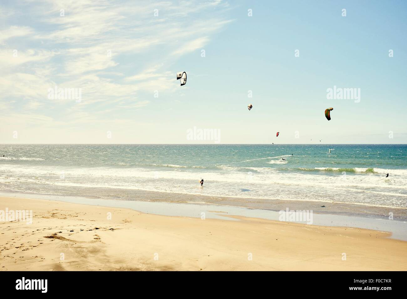 Distant view of small group of kitesurfers, Pacifica, California, USA - Stock Image
