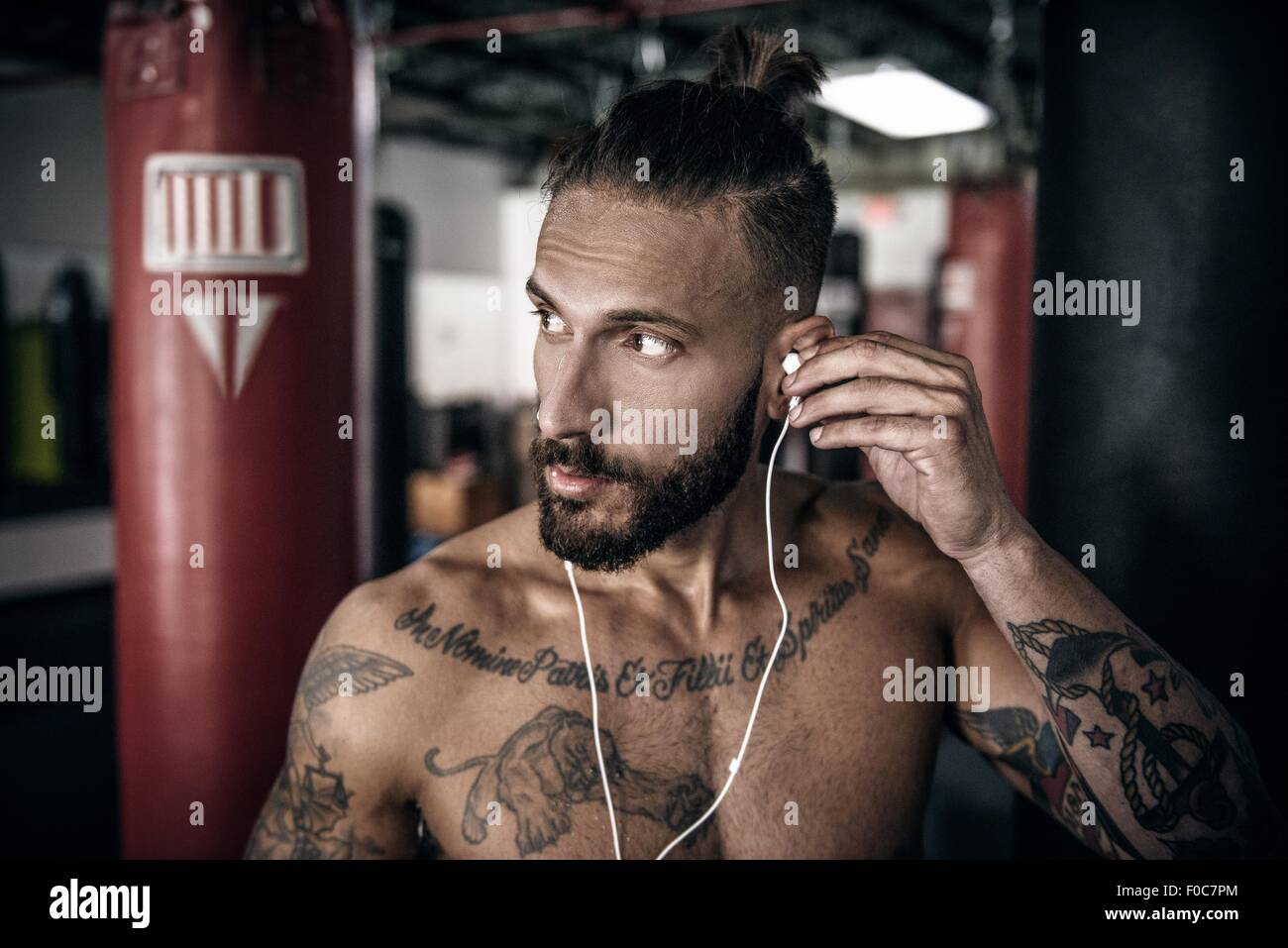 Male boxer inserting ear phones in preparation for training - Stock Image