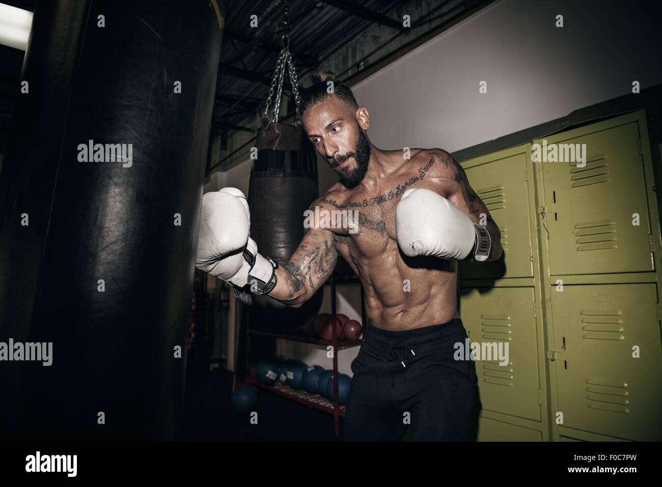 Male boxer training on gym punch bag - Stock Image