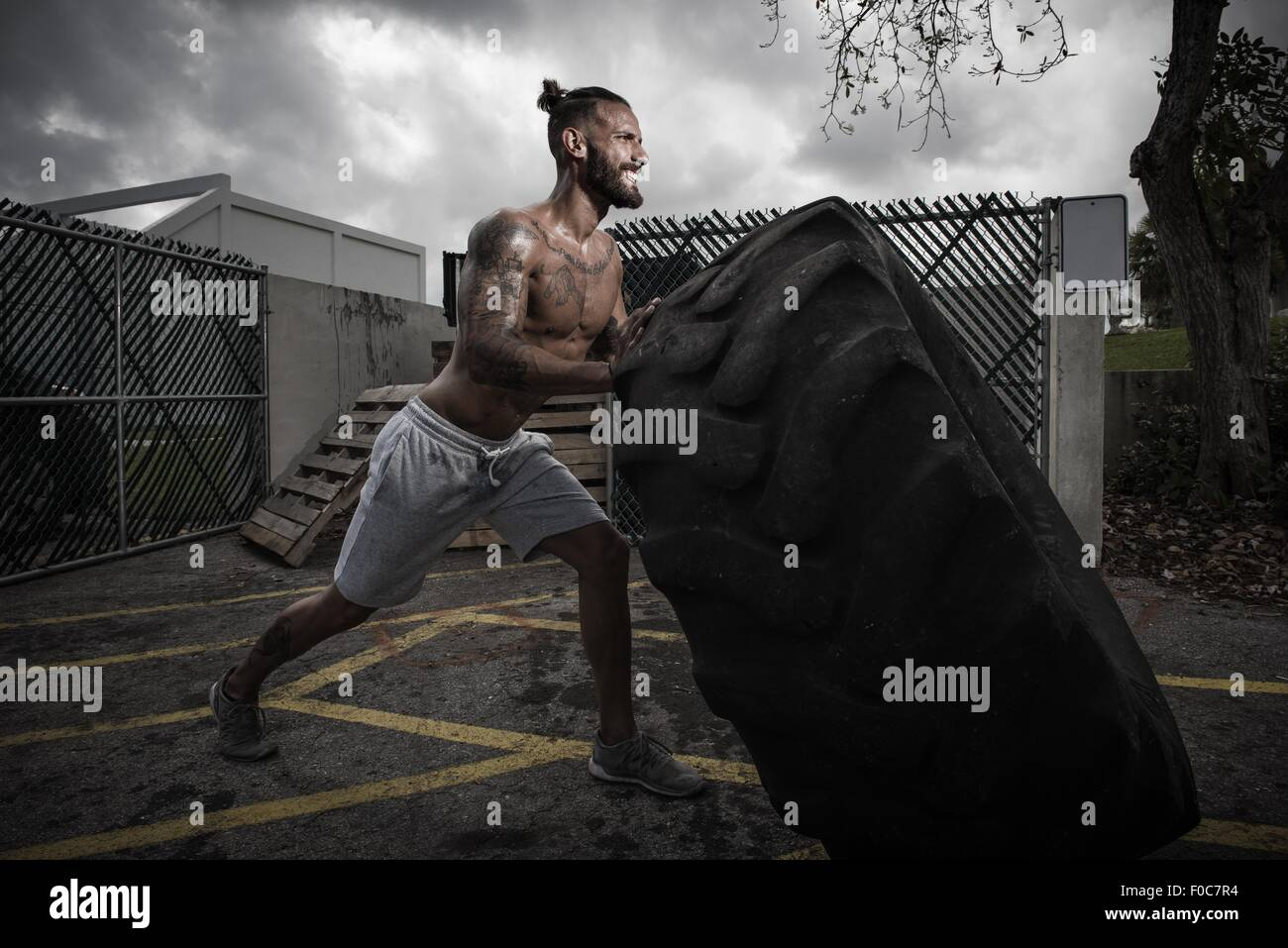 Male boxer with gritted teeth pushing truck tyre in yard - Stock Image