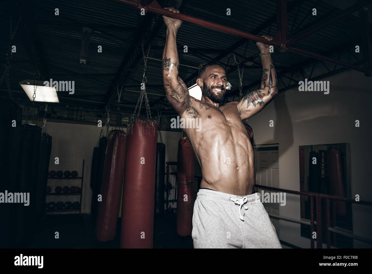 Male boxer doing pull ups with gritted teeth in gym - Stock Image