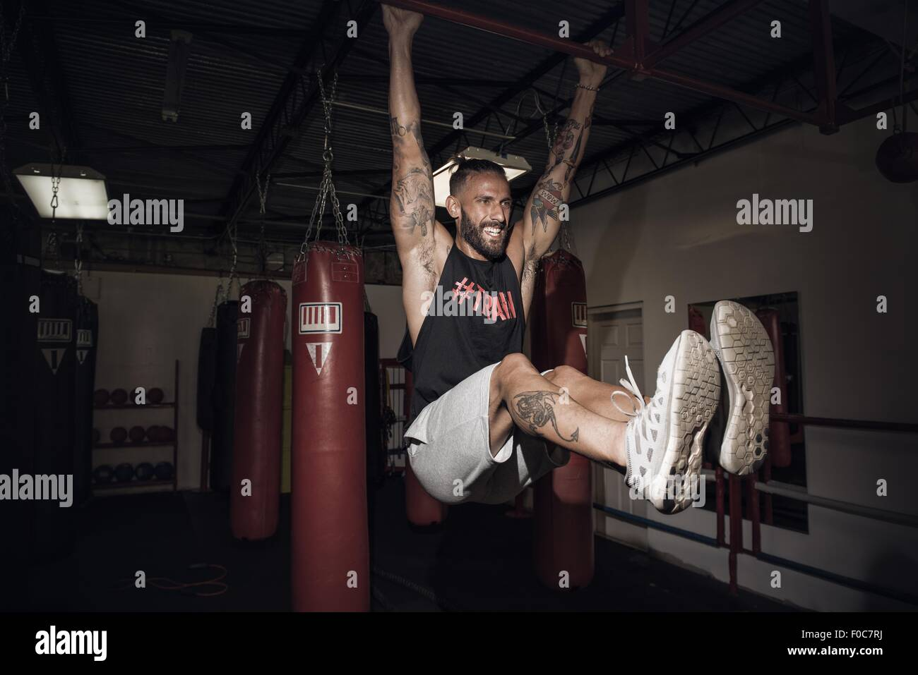Male boxer training on bar with gritted teeth in gym - Stock Image