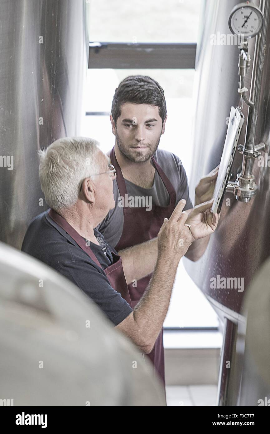 Brewers in brewery next to stainless steel tanks - Stock Image