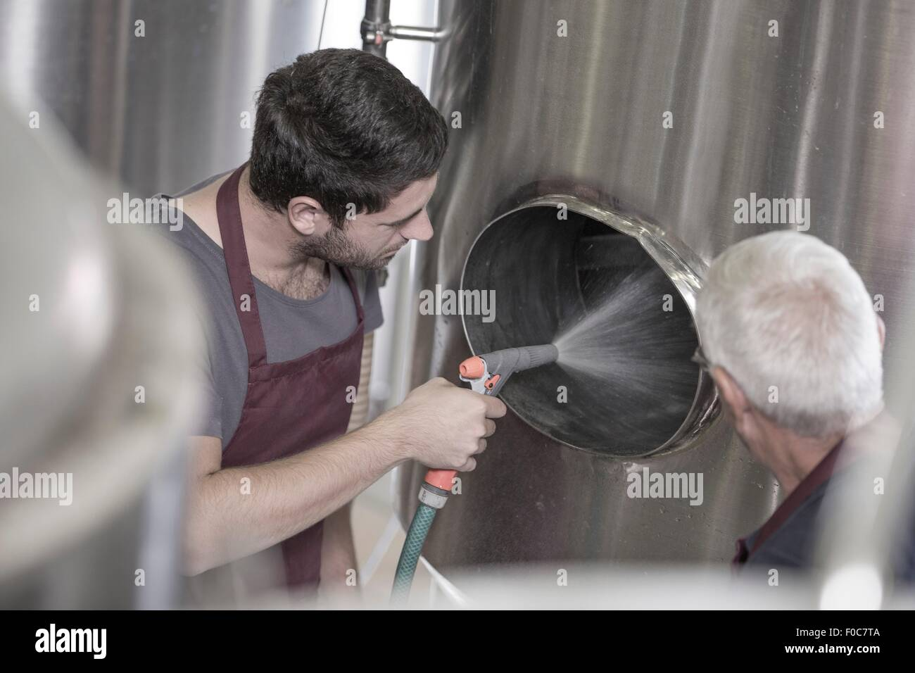 Brewer cleaning out a stainless steel tank in the brewery - Stock Image
