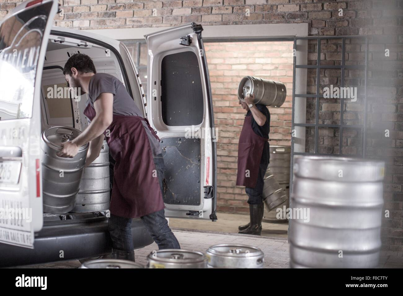 Brewers loading kegs into back of van - Stock Image
