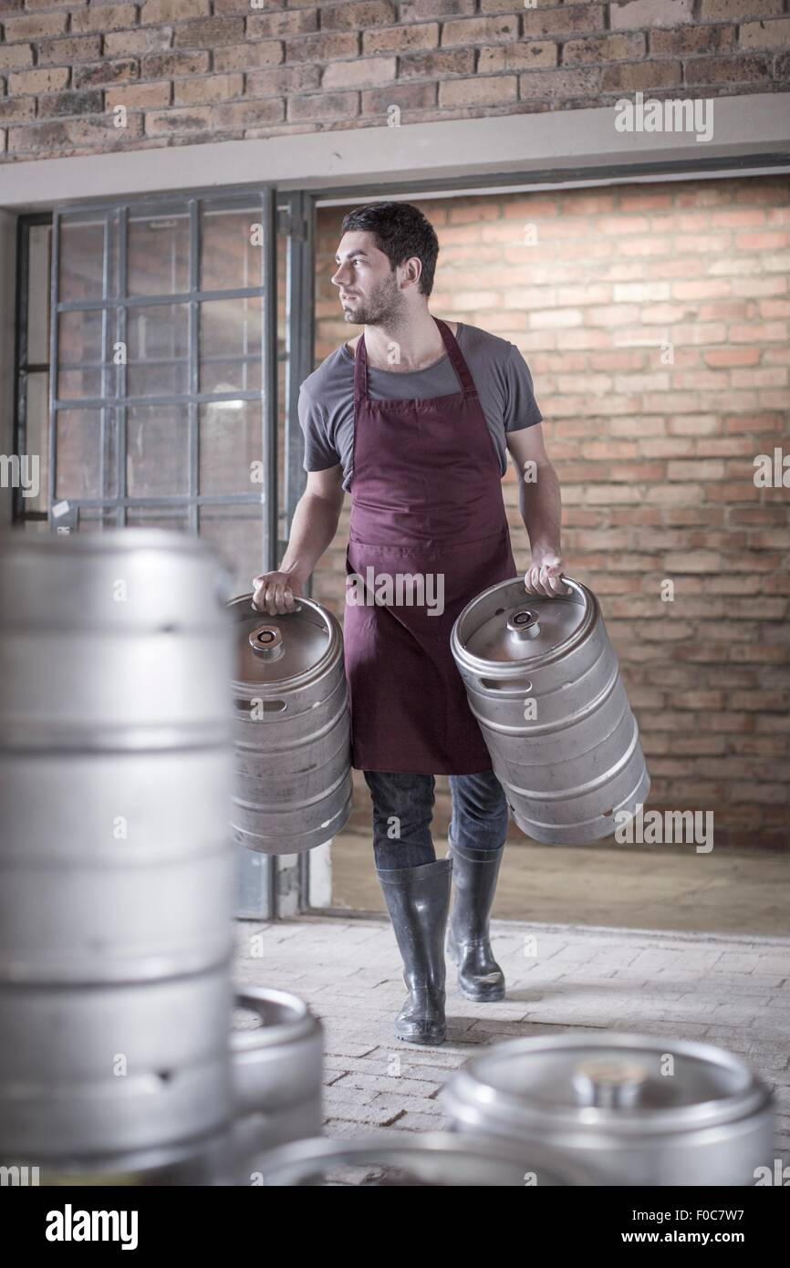 Brewer carrying two kegs of beer - Stock Image