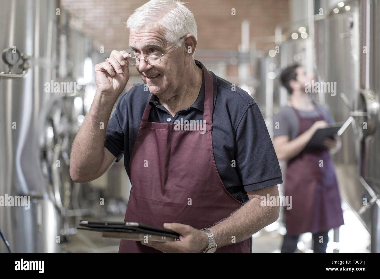 Brewers in brewery standing next to stainless steel tanks - Stock Image