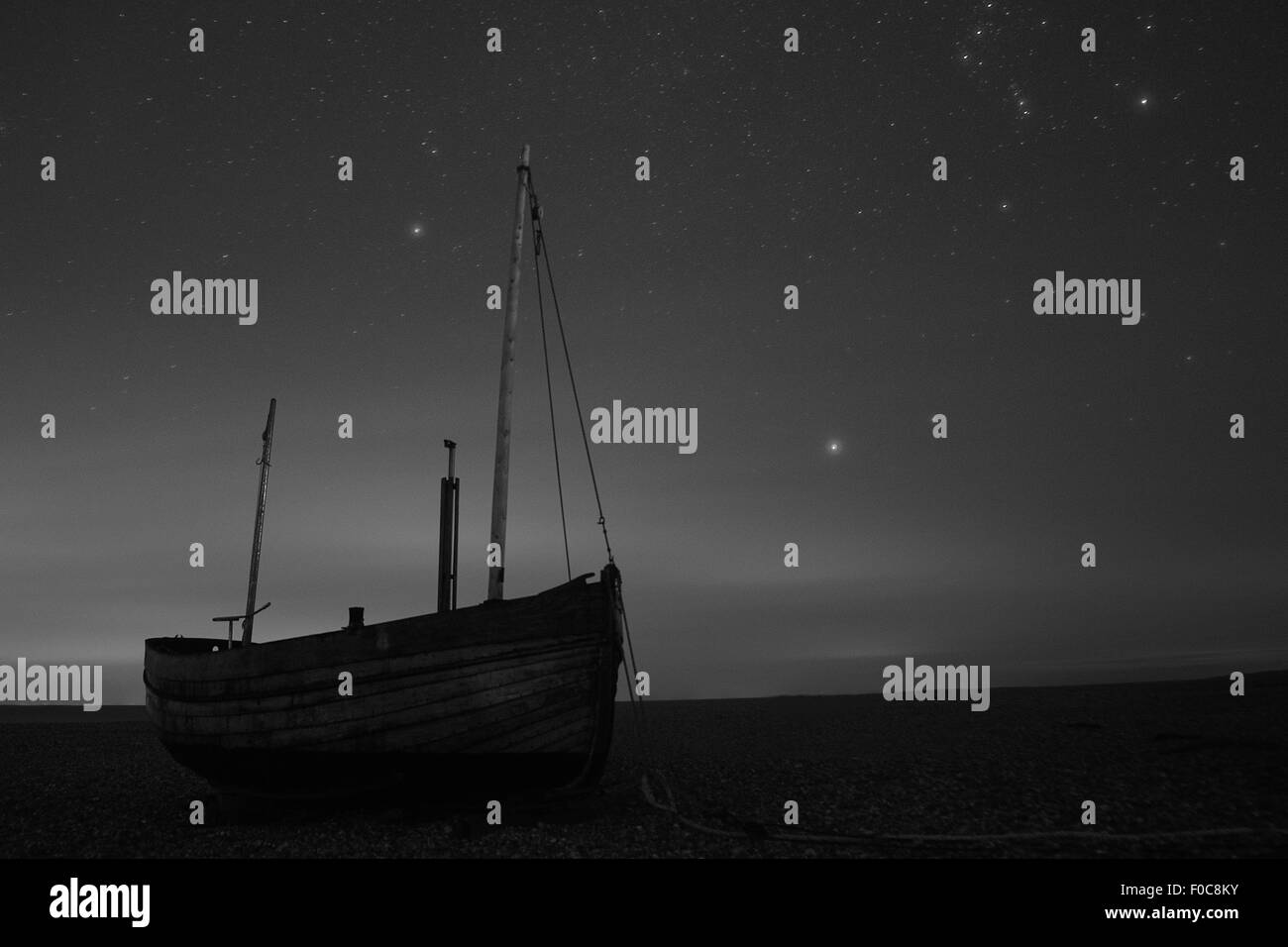 A wooden boat is seen on the beach at night, under a blanket of stars, in Dungeness, Kent, England, in black and - Stock Image