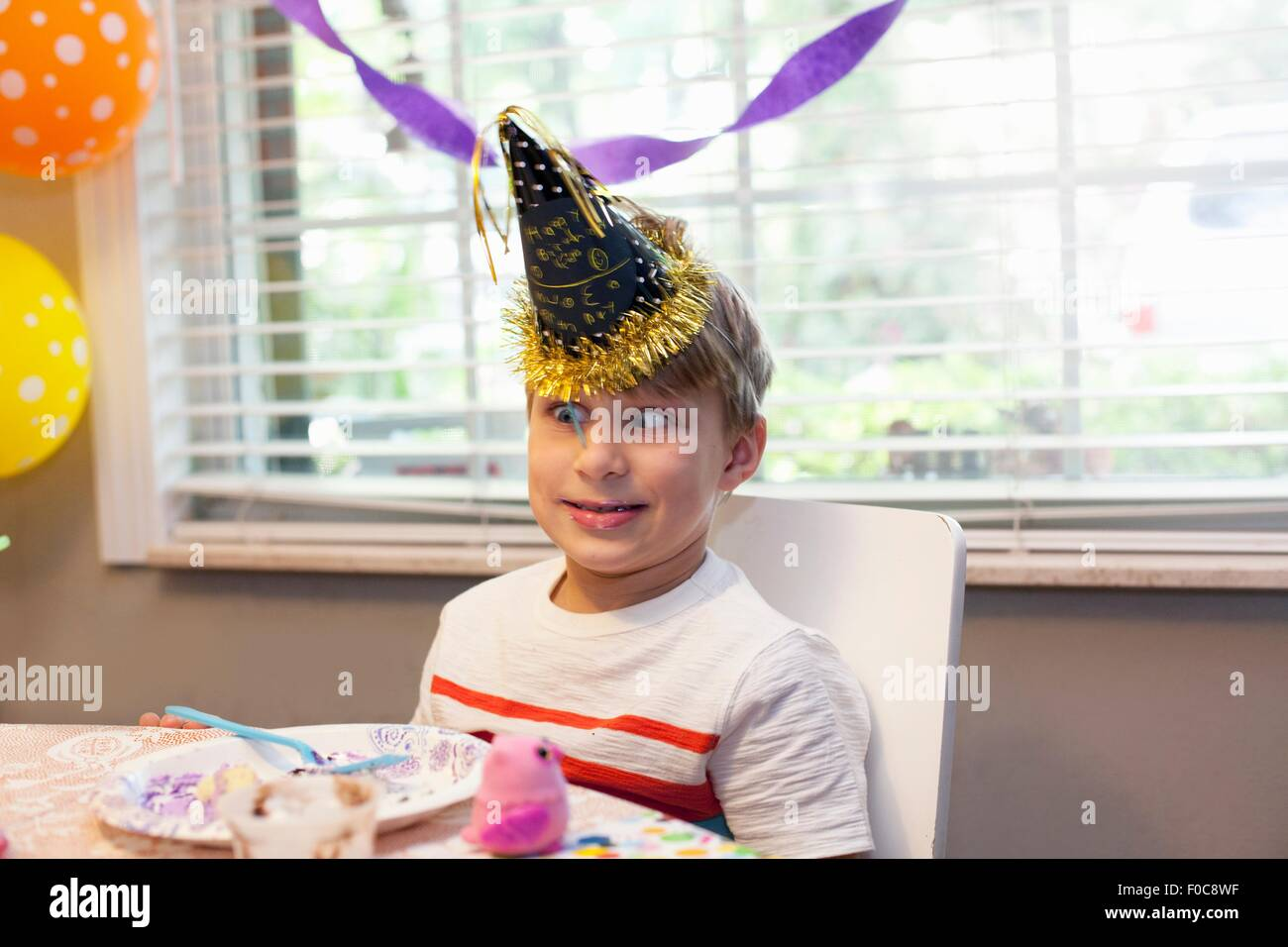Boy in party hat sitting at table eating birthday cake pulling funny face - Stock Image