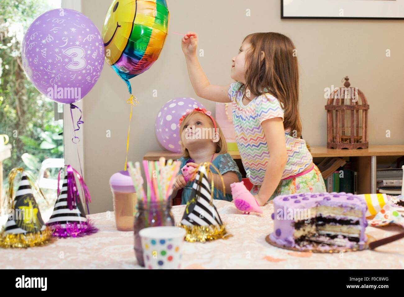 Two girls sitting at birthday party table with cake playing with balloons - Stock Image