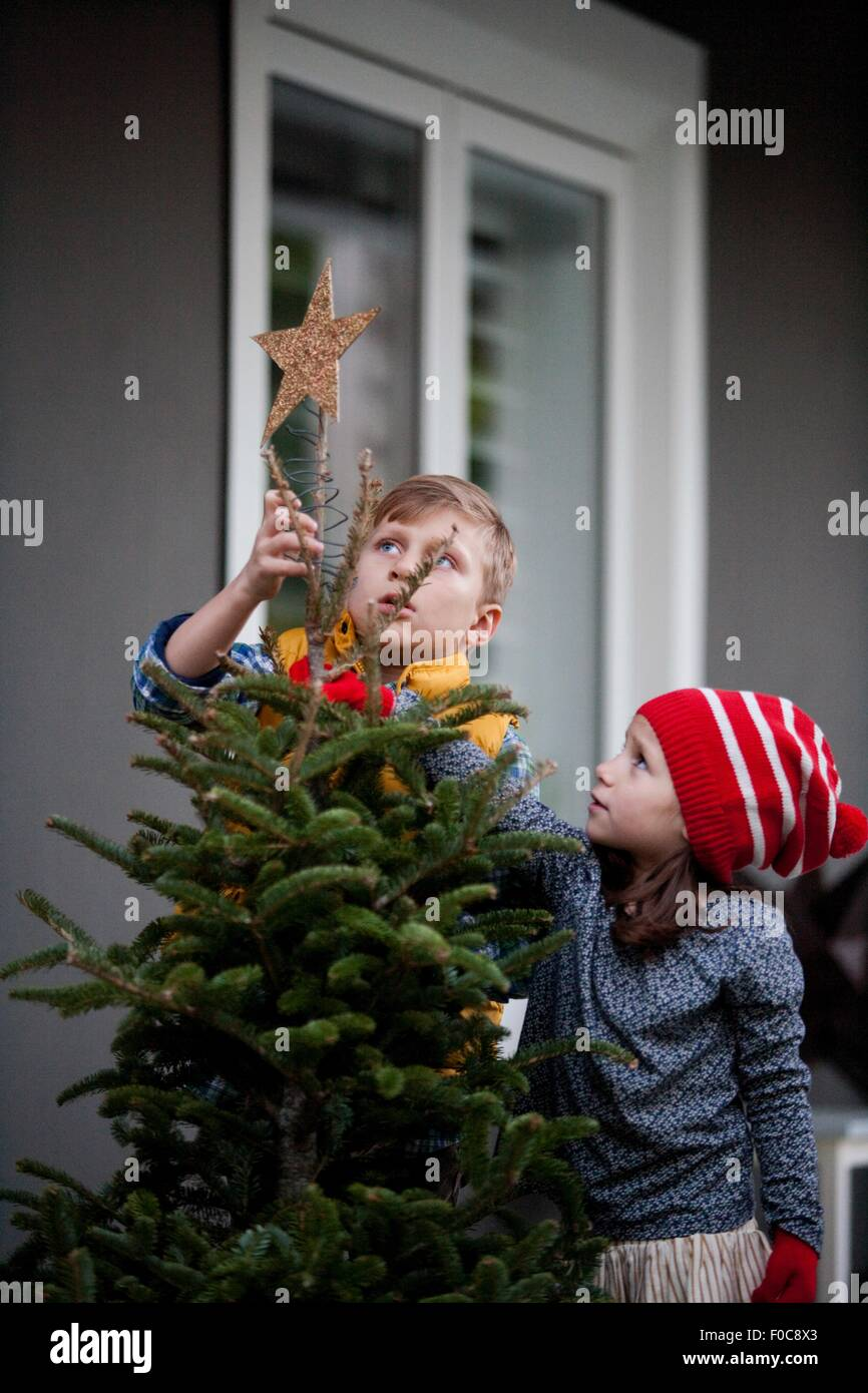 Portrait of a boy and girl putting star decoration on top of christmas tree - Stock Image