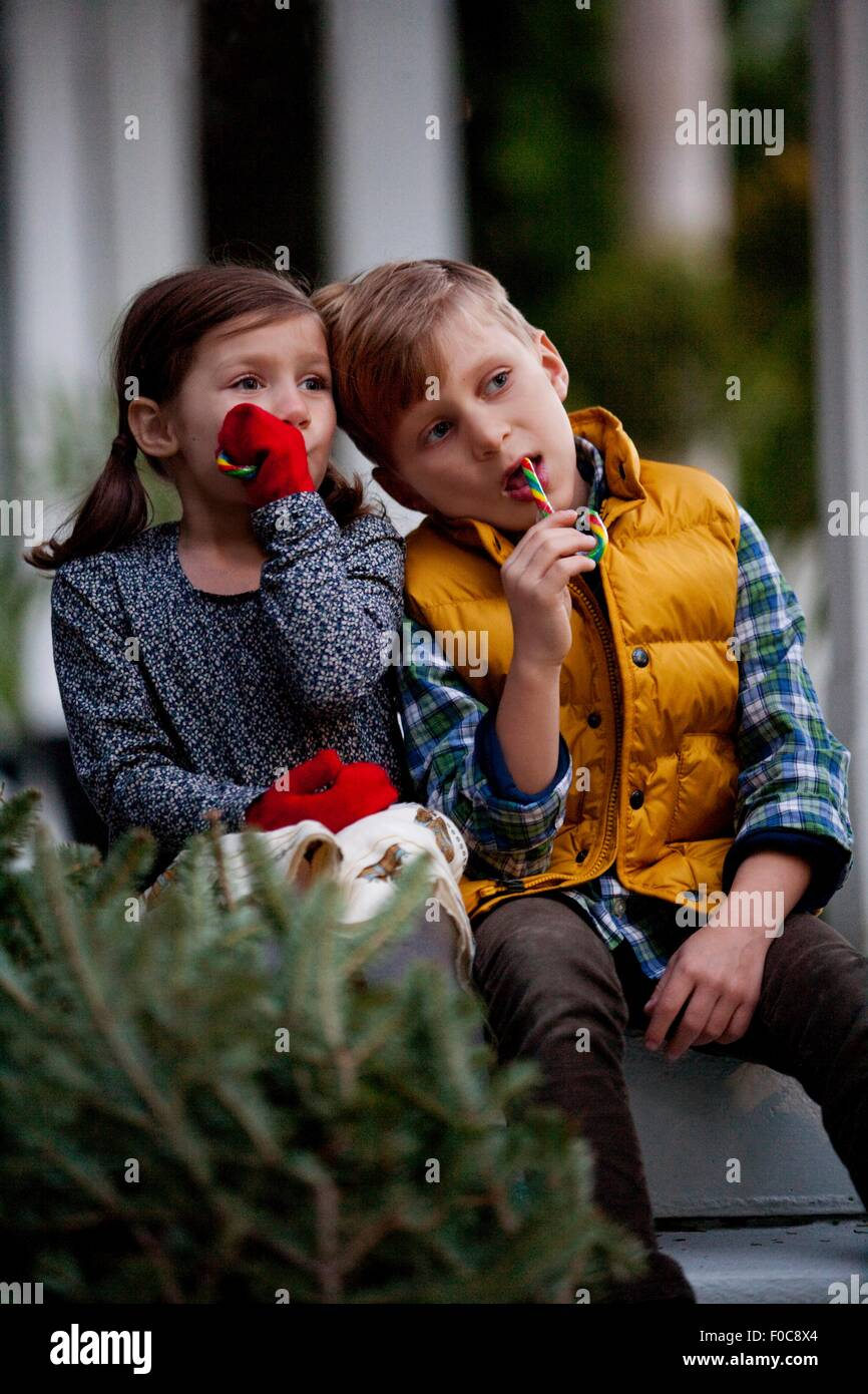 Portrait of a boy and girl eating festive candy canes - Stock Image
