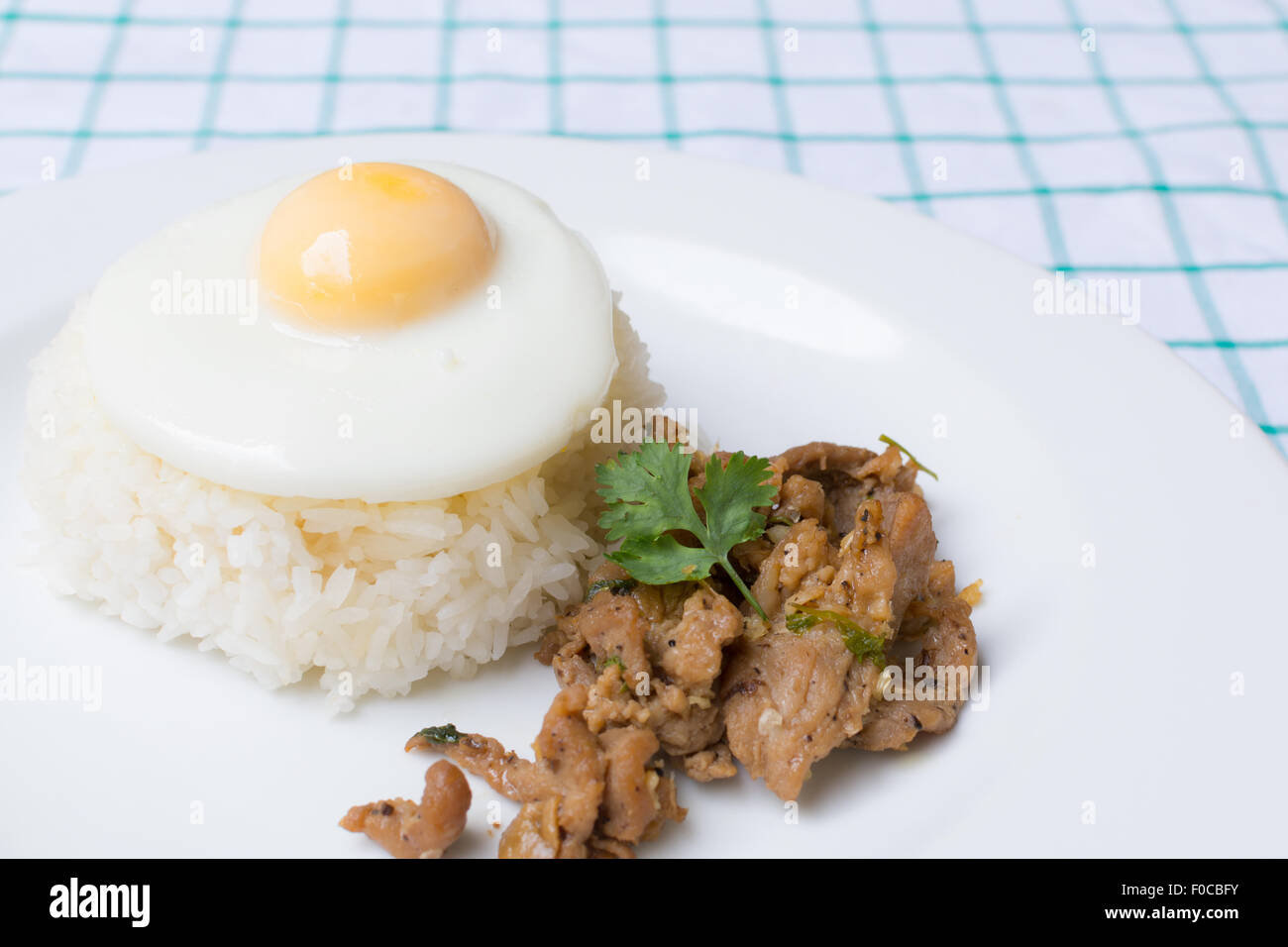 Pork fried with garlic and fried egg on rice - Stock Image
