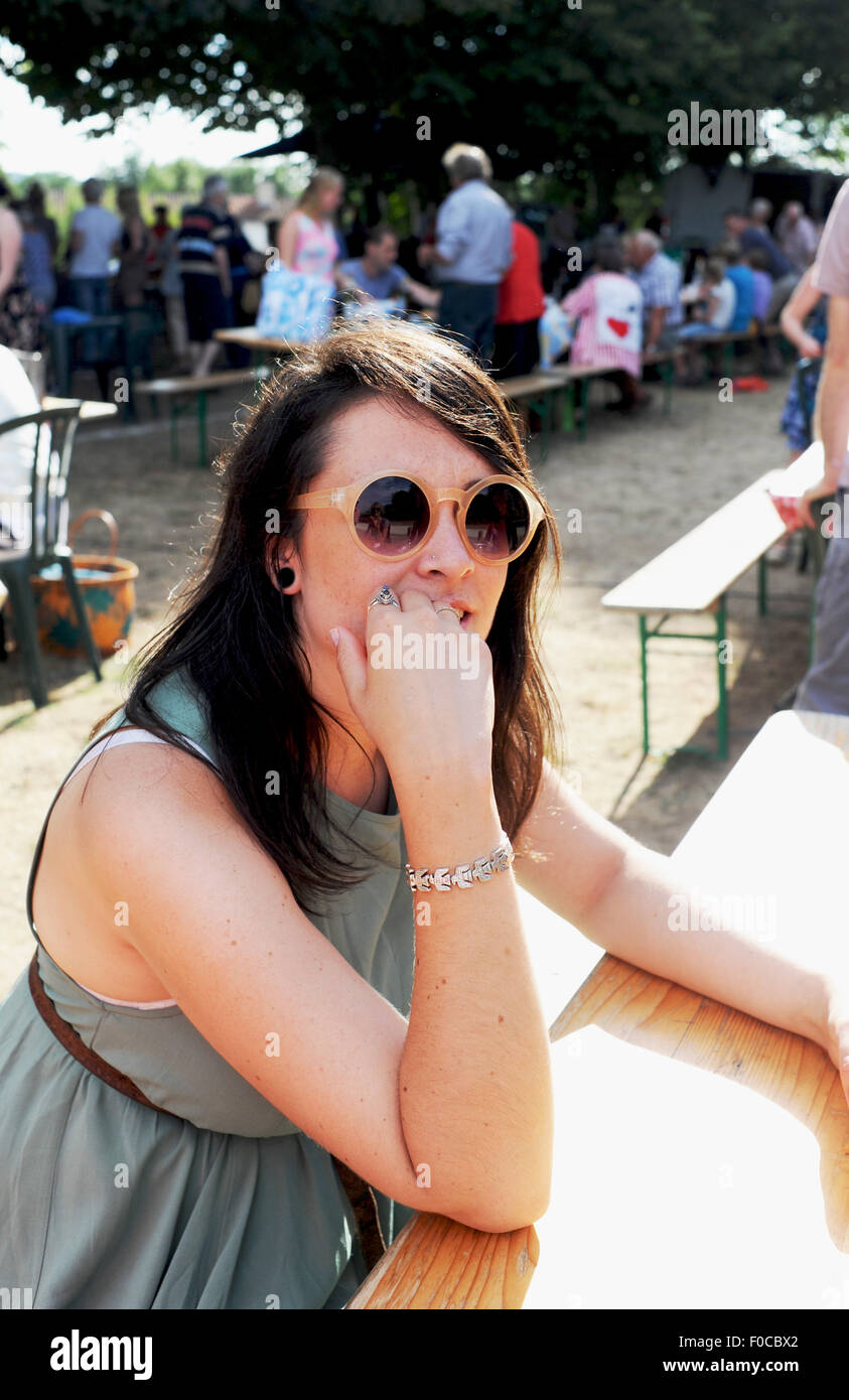 Young woman looking pensive on holiday at Picnic evening at Loubejac which is a small village in the Dordogne France - Stock Image