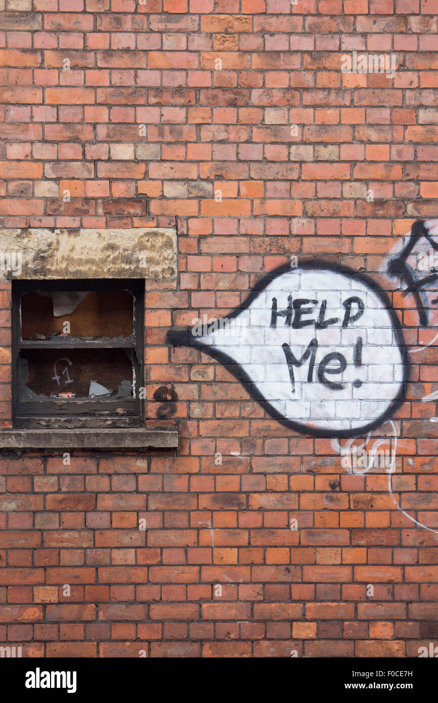 'Help Me!' graffiti words in speech bubble next to coming from broken smashed boarded up window on red brick - Stock Image