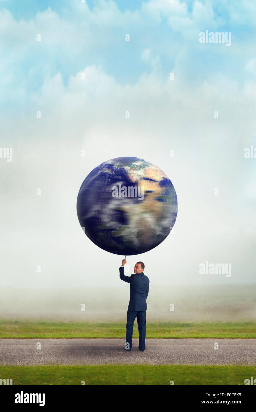 environmental business concept businessman holding spinning planet earth aloft with one finger - Stock Image