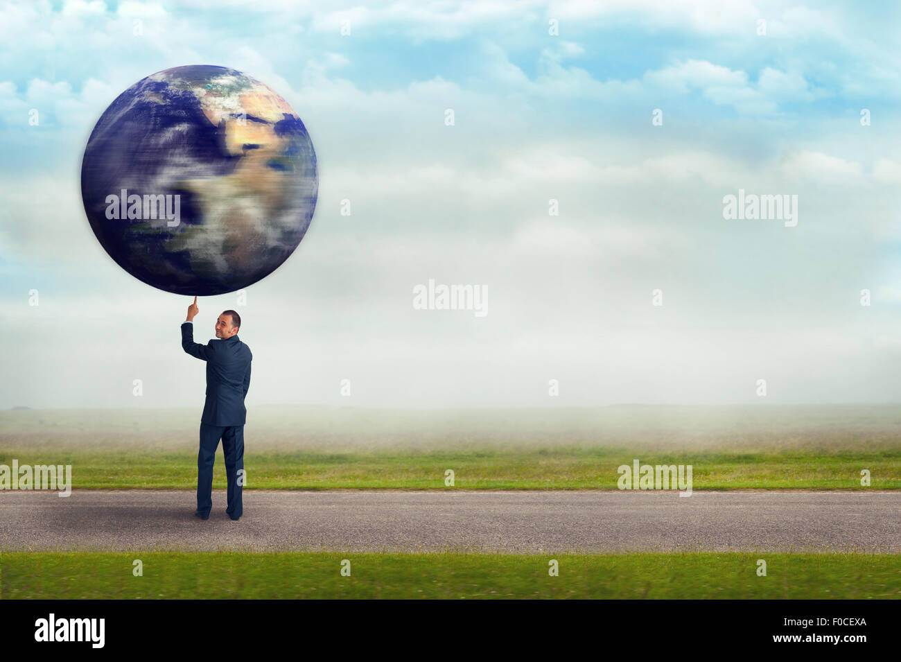 businessman holding spinning planet earth globe aloft with one finger - Stock Image