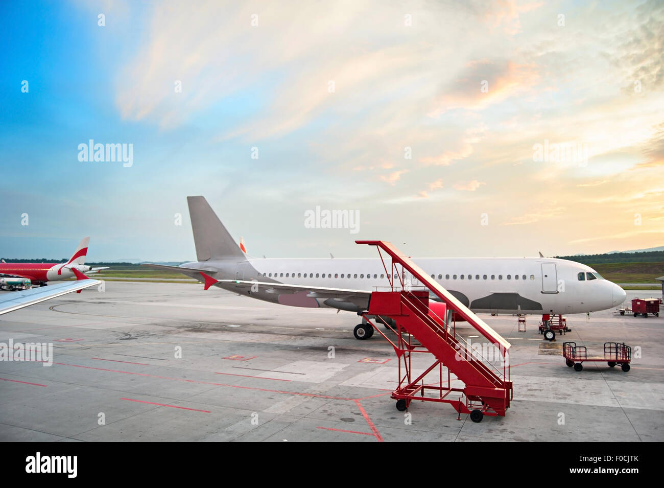 Airplaine at airport in the beautiful sunrise. - Stock Image