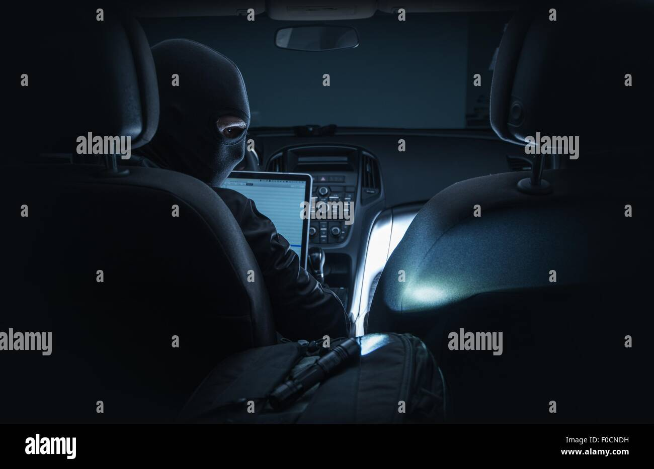 Hacking Car System. Car Hacker in Black Mask Hacking Vehicle Systems From Inside the Car Using Laptop Computer. - Stock Image