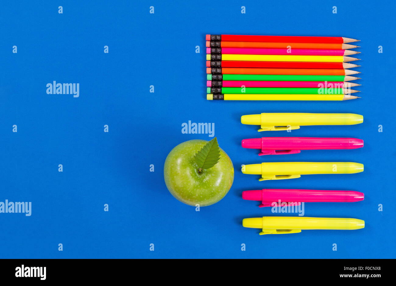 Office or back to school supplies consisting of a green apple, highlight markers and colorful pencils on blue background. - Stock Image