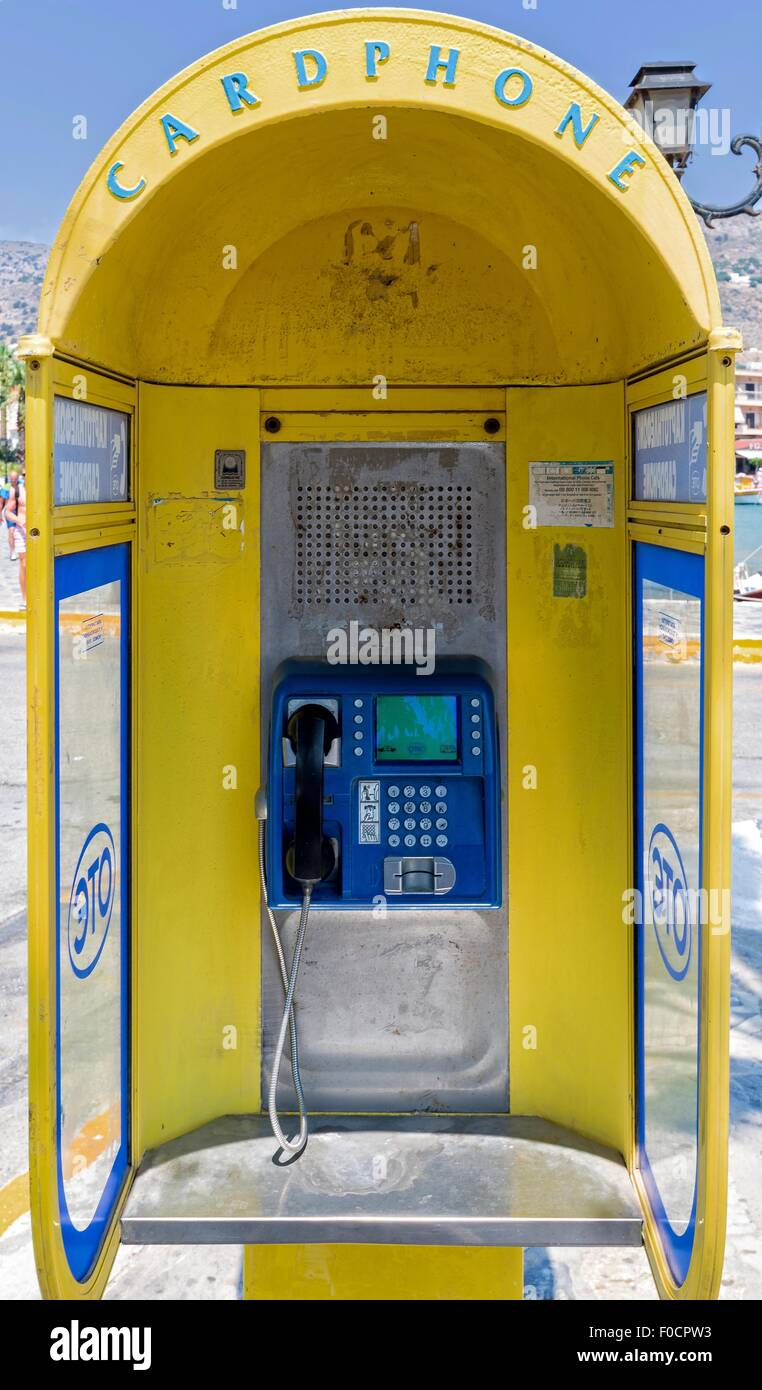 Greek telephone box for use with cards. Yellow. - Stock Image