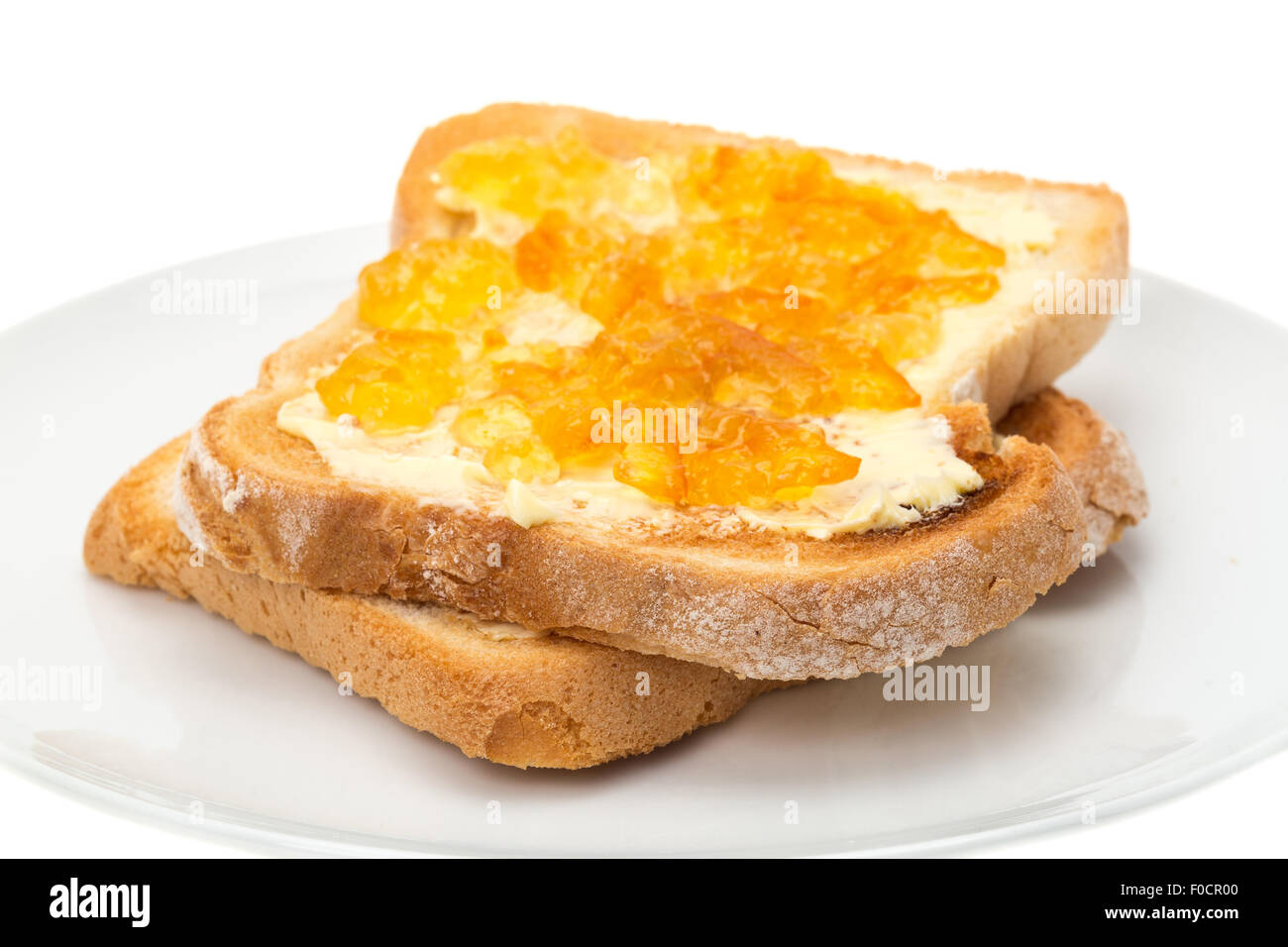 Orange marmalade on buttered toast - studio shot with a white background - Stock Image