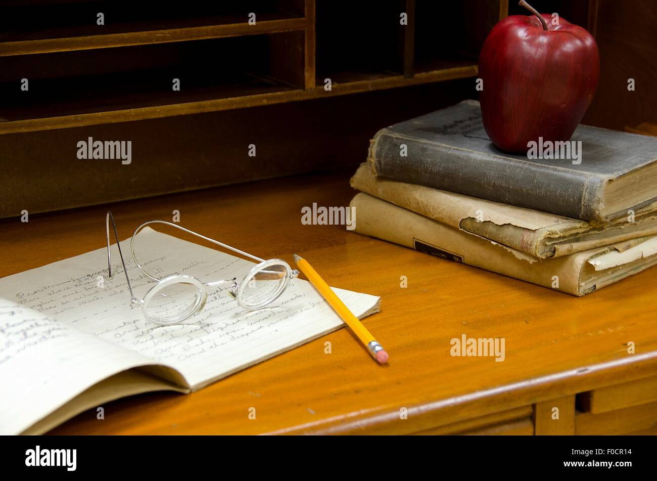 Old-fashioned eye glasses on notebook on antique teacher's desk. - Old-fashioned Eye Glasses On Notebook On Antique Teacher's Desk
