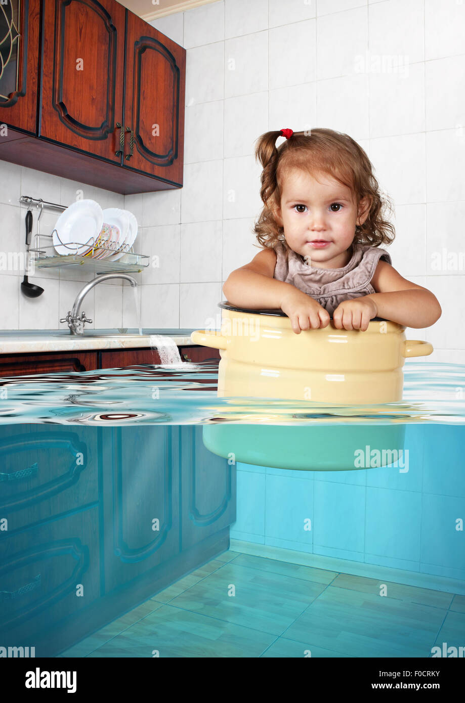 Funny little child swim in pan in the flooded kitchen, mess creative concept - Stock Image