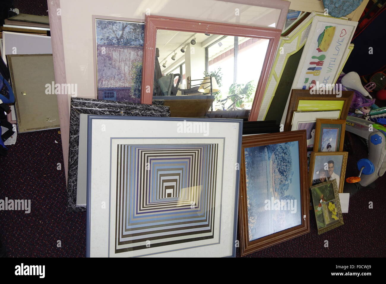 Thrift shop display of photos, mirrors and frames - Stock Image