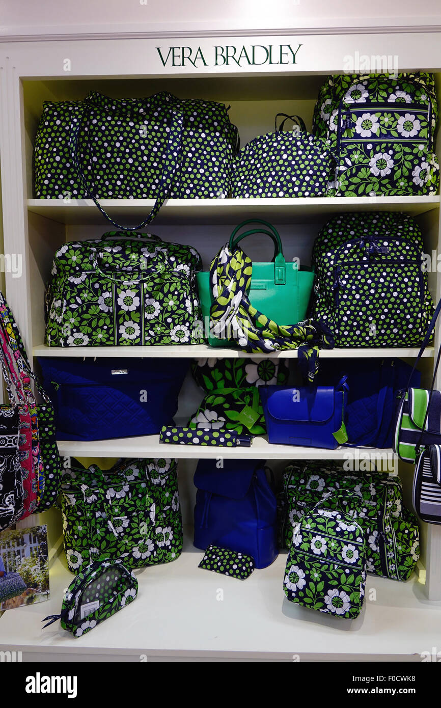 Shelves stocked with Vera Bradley handbags in a store - Stock Image