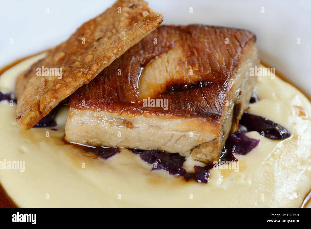 Pork belly with mash potato, red cabbage and an apple jus. - Stock Image