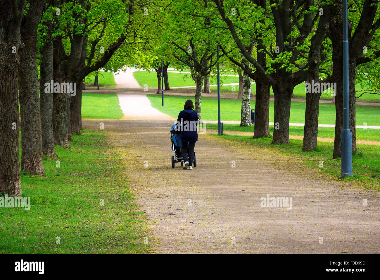 Woman with baby stroller walking in a city park - Stock Image