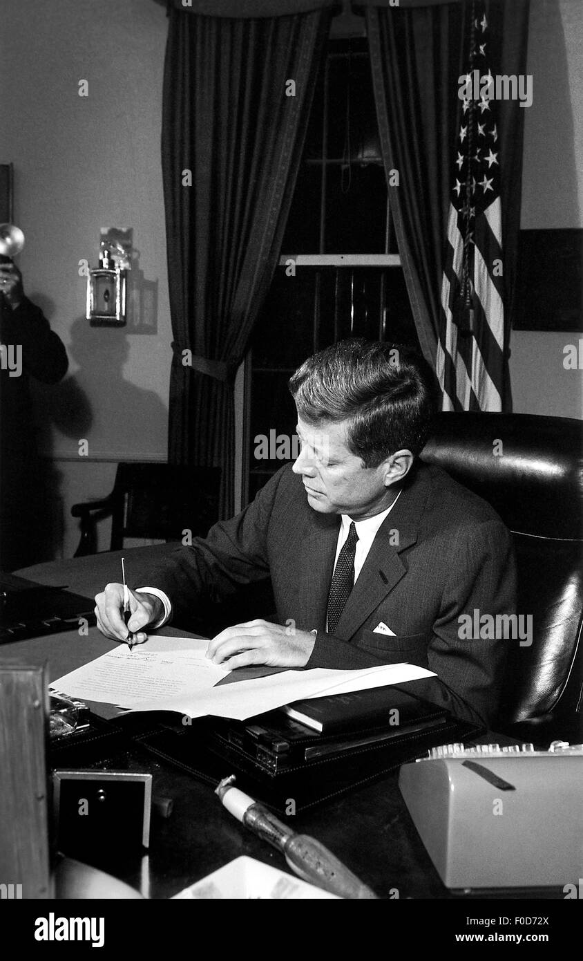 President John F. Kennedy signing the Cuba Quarantine Proclamation in the Oval Office. - Stock Image