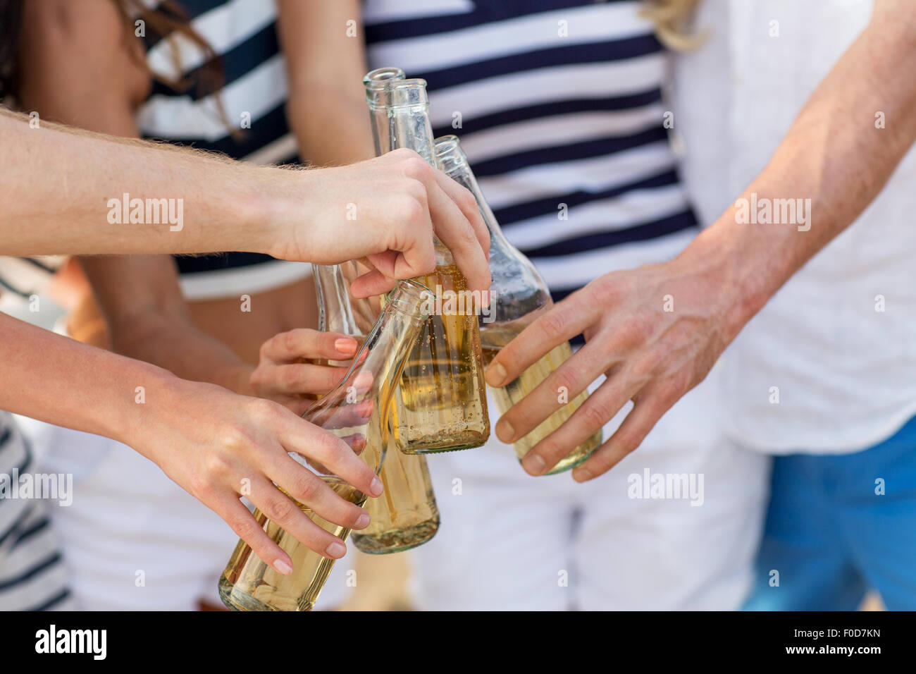 close up of hands clinking bottles with drinks - Stock Image