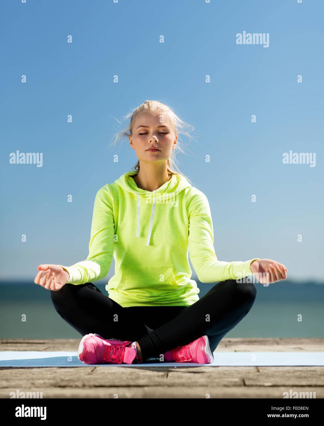 woman doing yoga outdoors - Stock Image